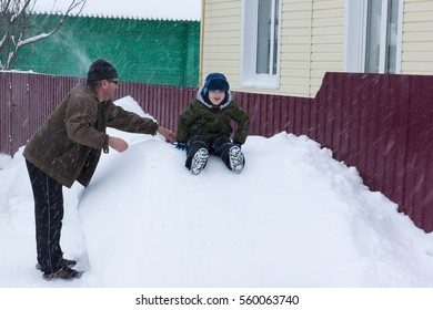 a little boy riding on a snowy hill in the care of grandparents