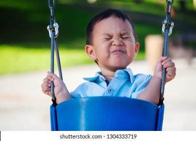 Little boy riding a playground swing with an expression of fear, holding on with a tight grip because he is scared.