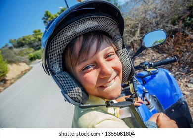 Little boy riding quad bike on Greece island. Cute child on quadricycle. Motor cross sports on Greece island. Kids summer vacation activity.