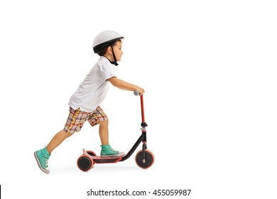 Little boy riding a scooter in a protective helmet isolated on a white background