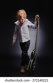 little boy rock star with a guitar. Black background