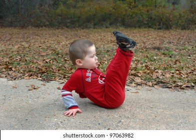 Little boy role plays the exercises he has seen his mom doing.  He is concentrating and lifting his legs into the air as he sits on the sidewalk and leans backwards.