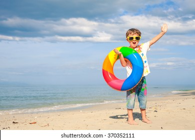 Little boy with rubber ring standing on the beach at the day time
