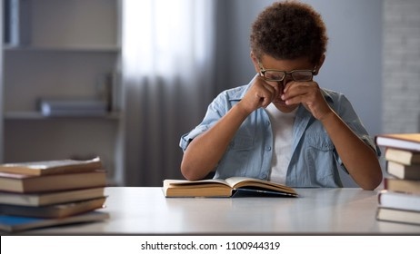 Little boy rubbing tired from active reading eyes, doing lots homework, studying