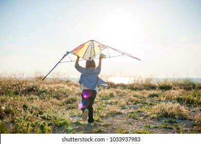little boy run across the field with a kite in his hands trying to fly