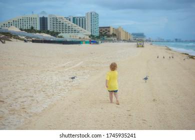 Little boy running along the summer beach with seagulls.