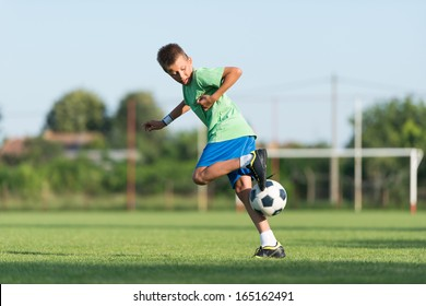 little boy running dribbling on the sports field