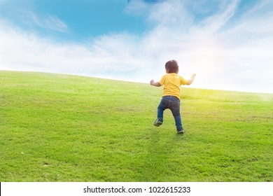 Little boy is running in the green field with nice blue sky and have sunny  day 94116e2272a0