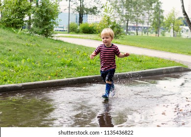 Little boy running into the puddle. Toddler playing in the park.