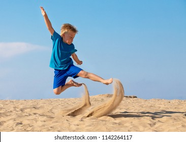 LITTLE BOY RUNNING AND JUMPING IN THE SAND, KID EXERCISING ON SANDY BEACH