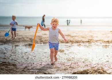 little boy running and laughing on the beach