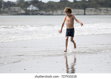A little boy is running on the beach, splashing in the water