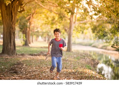 Little boy running in the park with happy face