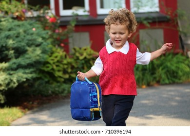 A little boy running to school with his back pack