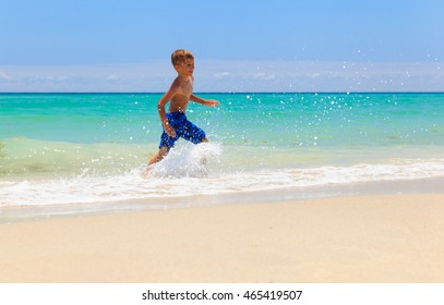 little boy running splashing water on beach