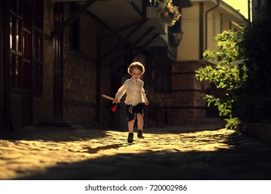 Little boy running with a sword in a sun beam. Nessebar, Bulgaria. Image with selective focus and toning.
