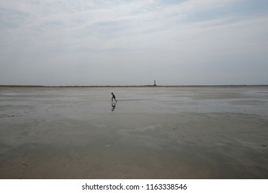 A little boy is running in the Wadden Sea in Ostfriesland