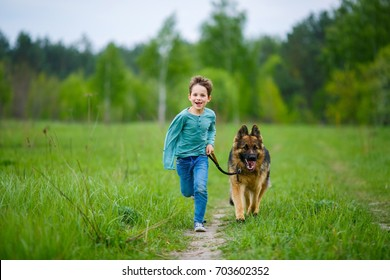 A little boy runs across the green meadow with his big German shepherd on a leash. The dog strained his ears and peered into the distance