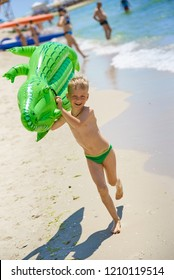 A little boy runs to swim on the beach with a large inflatable crocodile toy