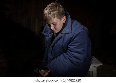 A little boy with a sad expression on his face, with outstretched hands, in which there is a bow. Poor boy, dressed in cheap, old, winter clothes, asks to eat.