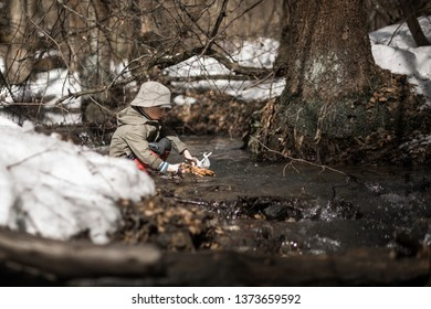 A little boy is sailing handmade toy boat in small forest river. Image with selective focus and toning.