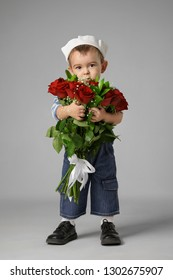 Little boy in a sailor suit with a bouquet of flowers