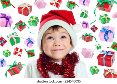 Little boy with Santa Claus hat and many gift boxes falling down isolated on white background