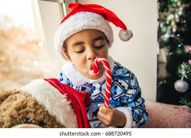 Little boy in a Santa Claus hat with teddy bear sitting on the window. The child is eating a Christmas candy.