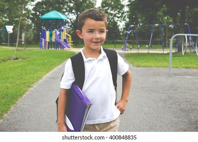 Little boy with school backpack and book in the play yard looking away from the camera