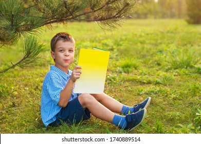 Little boy a schoolboy in a park at sunset reads a book. A surprised joyful child in a blue shirt with a yellow book in the park sits on the grass at sunset. Distance learning has ended.