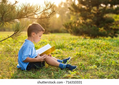 Little boy schoolboy in a park at sunset with a book.