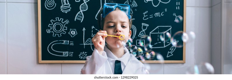 Little boy scientist playing with soap bubbles over table against of drawn blackboard