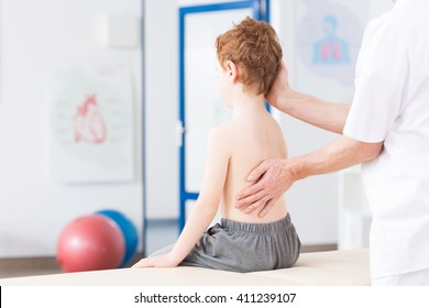Little boy with scoliosis in rehabilitation clinic. Physiotherapist working with special method on boy's spinal column