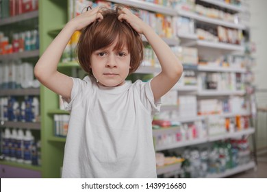 Little boy scratching his head, having lice, copy space. Little schoolboy with lice in his hair, scratching head at drugstore. Child suffering from dandruff