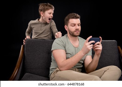 Little boy screaming at father using smartphone, family problems concept