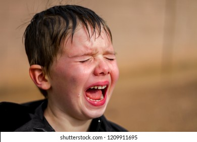 A little boy screaming at the top of his lungs in the middle of a temper tantrum.  A large tear rolls don his cheek and his face is bright red.  His mouth is wide open.