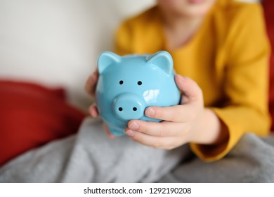 Little boy shaking a piggy moneybox and dreams of what he can buy. Education of children in financial literacy. Money saving concept.
