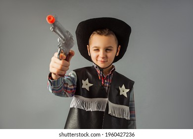 The little boy in a sheriff's costume is standing at the gray background. The boy is holding a toy gun