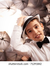 Little boy with shirt and bowtie looking at camera while holding his hat.