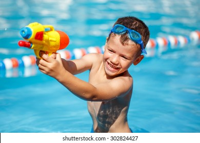 Little boy shooting with water gun in the pool