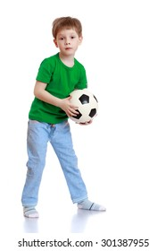 Little boy with short hair holding a soccer ball. A boy wearing a green T-shirt and blue jeans-Isolated on white background