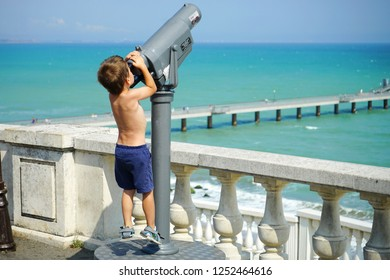 A little boy in shorts trying to reach the observation tube to see the beautiful blue sea. But its growth does not allow