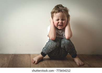 Little boy shouts covered his ears with his hands. Stressed child.  Space for text. sad and unhappy child. Upset toddler boy. problem child with head in hands