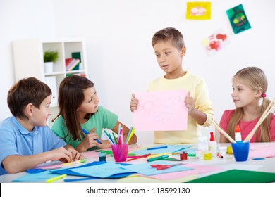 Little boy showing his drawing to his friends in classroom