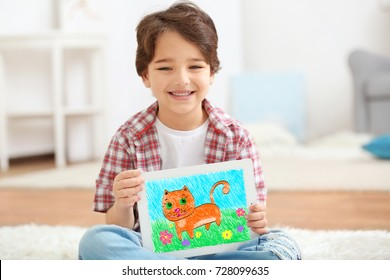 Little boy showing his drawing on tablet at home