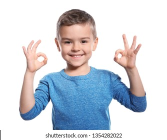 Little boy showing OK gesture in sign language on white background