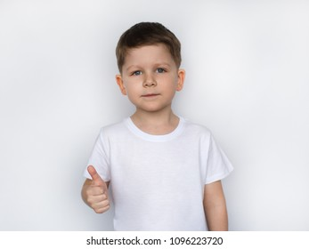 little boy showing thumbs up gesture in a white T-shirt isolated on white background. Space for Your Text. Ok sign