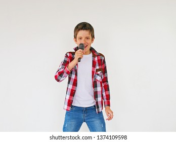 Little boy singing with microphone on grey background. Very emotional - Image