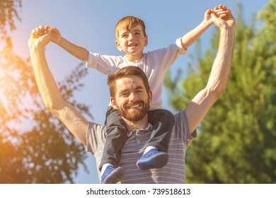 The little boy sit on the neck of father
