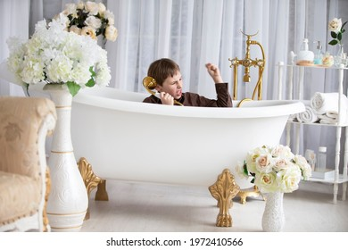 A little boy sits in the bathroom in his clothes and plays a telephone game. Talking on the phone is like a game.